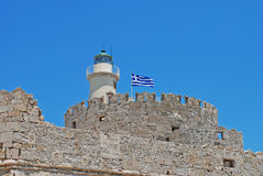 Fortress nad a lighthouse. Greek fortress with national flag and a lighthouse Stock Images