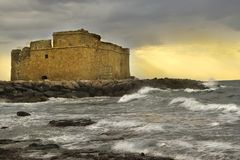 The fortress of the sea waves sunset beach clouds evening. At sunset the ancient fortress on the sea shore near the town of Paphos in Cyprus Royalty Free Stock Images