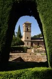 View through the green arch to the tower in the fortress of Granada. The fortress in the Spanish city of Granada is the remains of Moorish architecture of the Stock Images