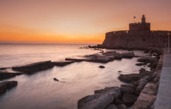 Fortress of St. Nicholas at dawn. Rhodes Island. Greece. Attraction of the island of Rhodes is the capital of the ancient port of Mandraki. Statue Colossus of stock photos