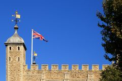 The fortress of Tower of London with British flag and wind vane or weather vane on top againt blue sky.  stock image