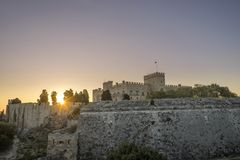 The fortress wall in the harbor at sunset. Rhodes Stock Photos