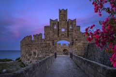 The fortress wall in the harbor at sunset. Rhodes Stock Photo
