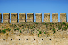 Fortress wall with loopholes. Ancient fortress wall with loopholes and transitions on the background of blue sky Royalty Free Stock Photos