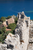Fortress wall of Simena Kalekoy. Castle shot on sunny day with wall in shapr focus and some trees and house rooftops and sea blurred Stock Photos