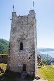 Fortress wall and tower of the ancient castle on the sea background Stock Image