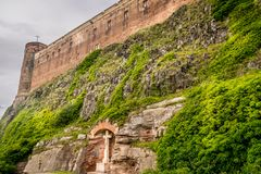 A castle wall on a cliff with christian cross in the cliff. royalty free stock photography