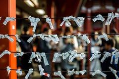 Fortuindocumenten aan kabels bij Japans heiligdom worden gebonden dat stock afbeeldingen