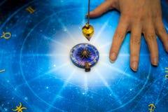 Fortuinteller met magische slinger op blauwe horoscoop zoals astrologie, dierenriem esoterisch onderwerp stock foto's
