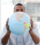 Fortunate businessman holding a terrestrial globe. In his office stock images
