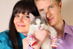 Fortunate young husband and wife hold cat Royalty Free Stock Image