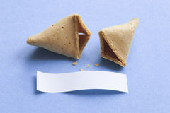 Fortune cookie with blank message. Broken fortune cookie with blank message on blue background Stock Photography