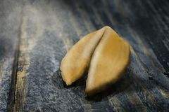 Fortune Cookie on wooden table with a piece of hope paper inside. Fortune cookie. A crisp and sugary cookie usually made from flour, sugar, vanilla, and sesame stock image