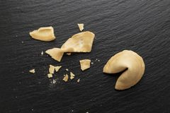 Fortune cookie crumbled. The fortune cookie is open and crumbled on a black slate background. place for text royalty free stock image
