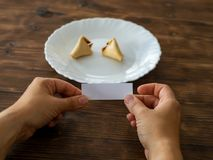 Woman holds the note from a fortune cookie in her hand. A Fortune cookie lies on a black plate on a light background with a blank note royalty free stock photos