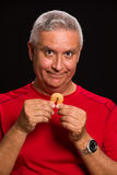Fortune cookie man. Handsome middle age man holding a chinese fortune cookie on a black background Stock Photography