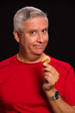Fortune cookie man. Handsome middle age man holding a chinese fortune cookie on a black background Royalty Free Stock Photos