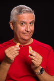 Fortune cookie man. Handsome middle age man holding a chinese fortune cookie on a black background Stock Photos