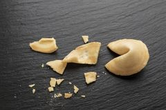 Fortune cookie open. The fortune cookie is open and crumbled on a black slate background. place for text royalty free stock images