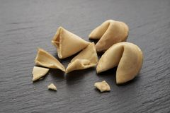 Fortune cookie open. The fortune cookie is open and crumbled on a black slate background. place for text royalty free stock photo