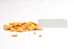 Fortune Cookie Slip. Crumbled fortune cookie with blank off-white slip against white background Royalty Free Stock Image