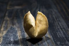 Fortune Cookie on wooden boards with a piece of hope paper inside. Fortune cookie. A crisp and sugary cookie usually made from flour, sugar, vanilla, and sesame royalty free stock photography