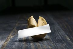 Fortune Cookie on wooden table with a blank sheet of hope paper. Fortune cookie. A crisp and sugary cookie usually made from flour, sugar, vanilla, and sesame royalty free stock photos