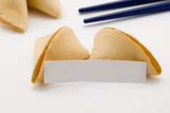 Fortune cookies and blank message. Opened fortune cookie with blank fortuneOpened fortune cookie with blue chopsticks in background Stock Photo