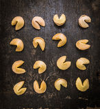 Fortune Cookies selection laid in a row on dark rustic background Royalty Free Stock Image