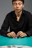 The fortune is on my side. Young gambler man in black shirt sitting at the playing table  on black background Royalty Free Stock Photography