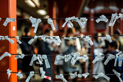 Fortune papers tied to ropes at Japanese shrine stock images
