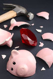 Fortune in a piggy bank business & finance concept. Broken piggy bank revealing a ruby conveying a sense of luck, fortune and wealth. Business & Finance Royalty Free Stock Photos
