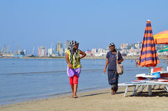 Fortune-taller gypsy women make their living on the beach of Durres, Albania. DURRES, ALBANIA – September 01, 2015: Fortune-taller gypsies walking on the beach Stock Photo
