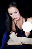 Fortune Teller. The girl leaned over the fortune-teller of ancient books Royalty Free Stock Photography