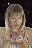 Fortune teller. Holding a crystal ball with images of paradise royalty free stock photography