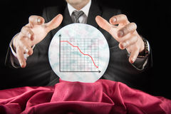 Fortune teller businessman, sees falling graph in a crystal ball Royalty Free Stock Image