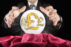 Fortune teller businessman, sees pound - Sterlin sign in a crystal ball Royalty Free Stock Photos