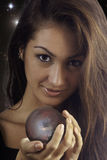Fortune teller with crystal ball. Young woman with a crystal ball with a tropical scene inside royalty free stock photos
