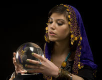 Fortune-teller with Crystal Ball. Gypsy fortune-teller uses a crystal ball to foretell the future stock image