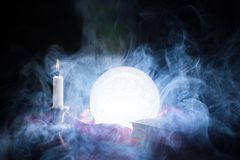 Fortune teller crystal ball smokes and lights on table stock images