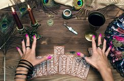 Tarot cards. Fortune teller female hands and tarot cards on wooden table. Concept of divination stock photos