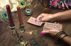 Tarot cards. Fortune teller female hands and tarot cards on wooden table. Concept of divination stock photography