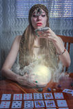 Fortune teller gazing in a crystal ball. Young female soothsayer predicting the future with her magic shining orb Stock Image