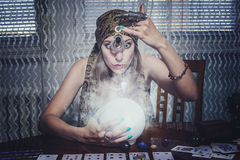 Fortune teller gazing in a crystal ball. Young female soothsayer predicting the future with her magic shining orb Stock Photo