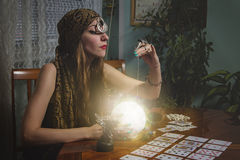 Fortune teller gazing in a crystal ball. Young female soothsayer predicting the future with her magic shining orb Royalty Free Stock Photography