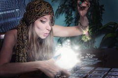 Fortune teller gazing in a crystal ball. Young female soothsayer predicting the future with her magic shining orb royalty free stock image
