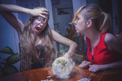 Fortune teller giving bad news. Soothsayer reacting badly, seeing a couple in a fight, terrified to break the bad news to her customer Royalty Free Stock Images