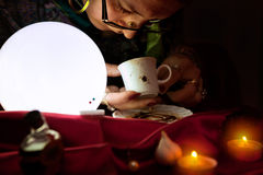Fortune teller looking and read a fortune from coffee mug Stock Photography