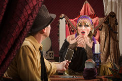Fortune Teller Predicting Bad Luck. Frightened European female fortune teller looking at card stock images