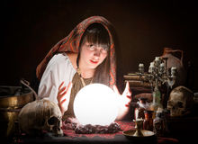 Fortune-teller predicting the future. Young fortune-teller reading the future in a crystral ball Royalty Free Stock Photos